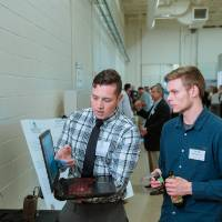 A student explaining something on a laptop to guests at the Engineering Design Project Preview